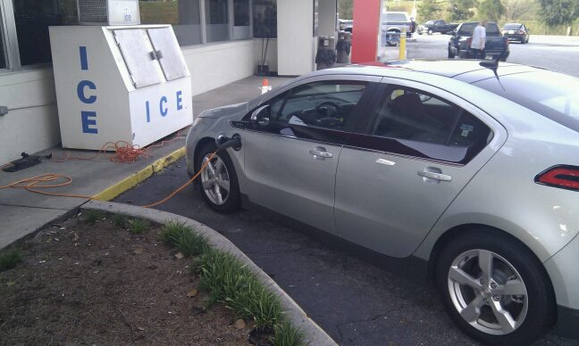 Chevy Volt plugged in to an outlet at a gas station